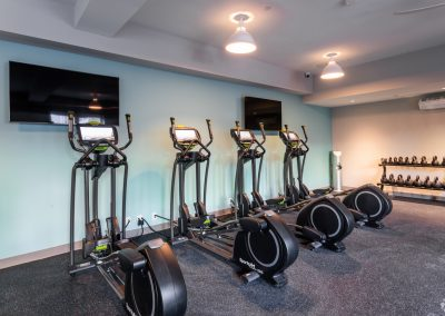 Gym with elliptical machines and kettle balls at the Residences at Bentwood in Plymouth Meeting